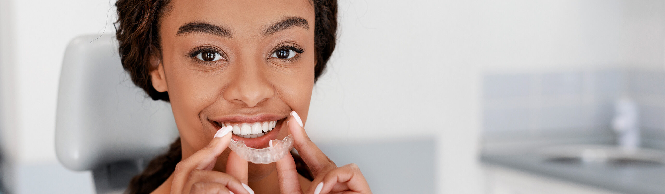 smiling woman putting clear aligners on her teeth