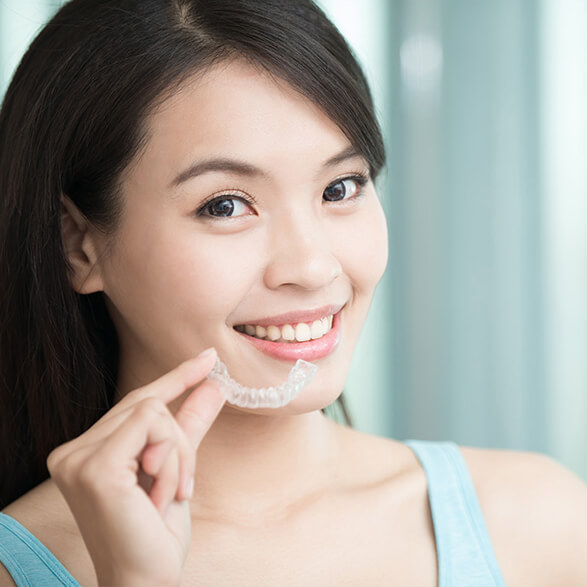 woman holding up her clear aligners