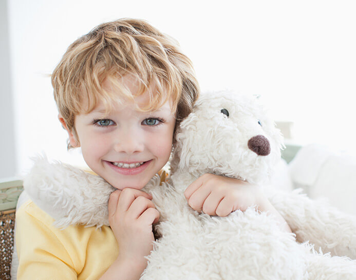 young boy holding his teddy bear