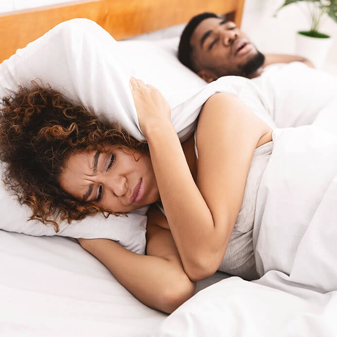 woman covering her ears with her pillow to drown our her husband's snoring