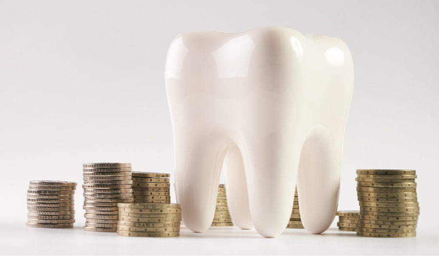 Tooth surrounded by stacks of coins to encourage patients to use their dental insurance benefits before year's end