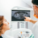 Brunette woman listens to her dentist as he points at her dental X-rays and discusses her oral health