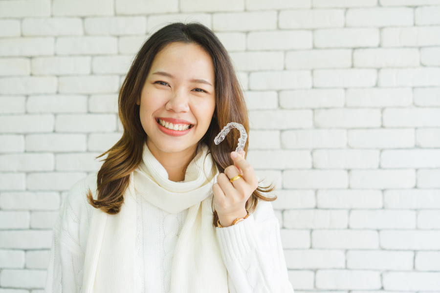 Brunette woman smiles while holding Invisalign clear aligner trays to straighten teeth