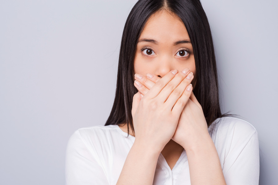 Dark-haired woman covers her mouth in embarrassment due to bad breath