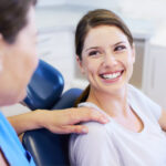 Brunette woman smiles while visiting the dentist for your biannual checkup and cleaning in Cedar Park, TX