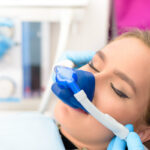 Brunette woman relaxes in the dental chair while wearing a blue nose mask administering nitrous oxide dental sedation