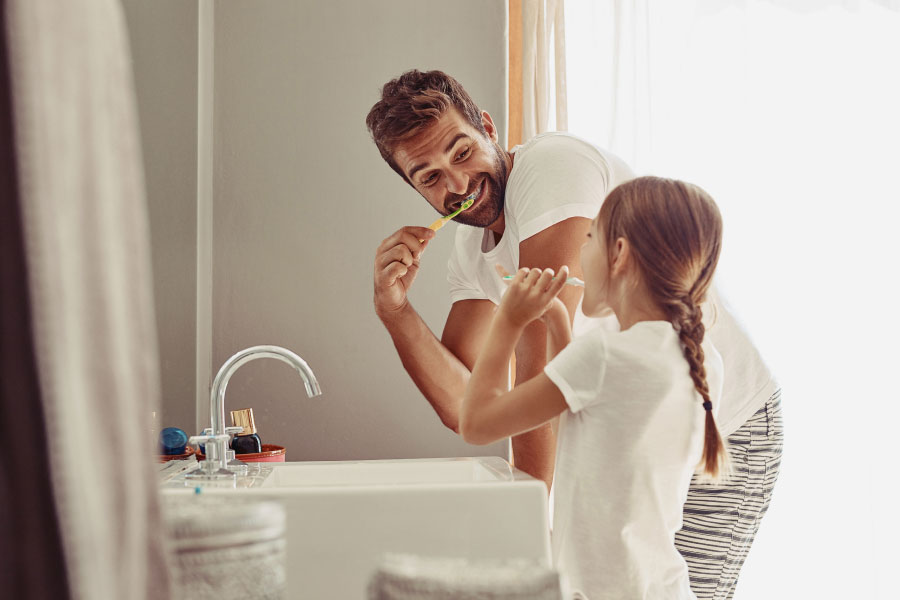 father and young daughter brushing away plaque together