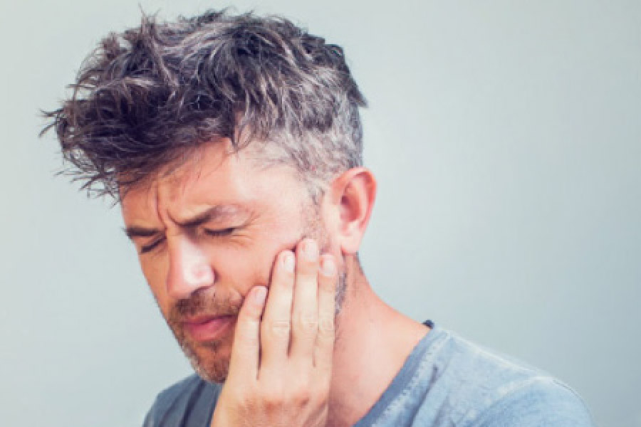 man holding his jaw in pain with dental trouble