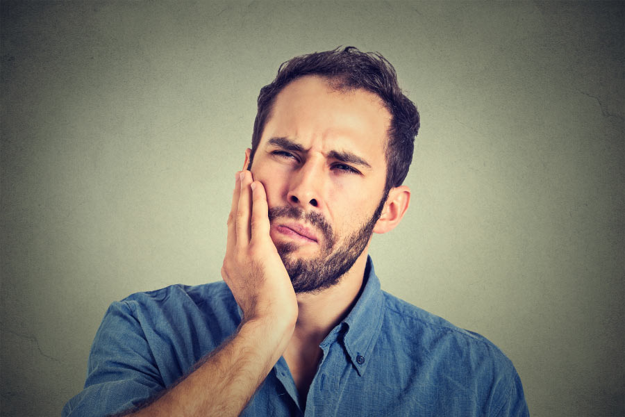 bearded man holds his jaw in pain after a night of teeth grinding