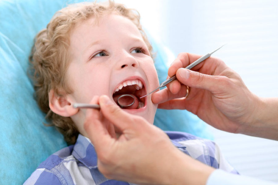 young boy in the dentist chair getting a checkup