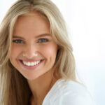 blond woman smiles showing off the results of professional teeth whitening