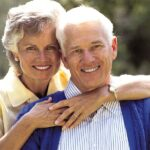 senior couple hug and smile showing off their healthy teeth
