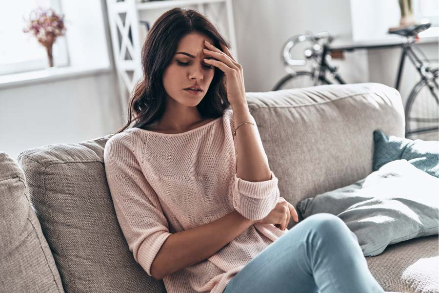 young woman sits on a couch holding her head in pain from a migraine headache