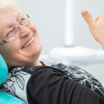 senior woman in the dentist chair gives a thumbs up after learning about diabetes and oral health